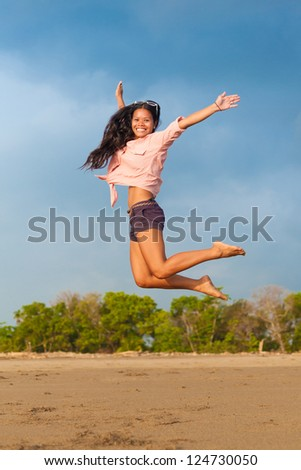 young woman jumping in the air on the beach - stock photo
