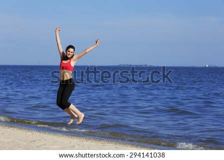 Young woman jumping on beach - stock photo