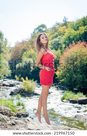 Young woman jumping or flying on cliff edge over fast mountain river on summer or early autumn outdoor copy space background  - stock photo