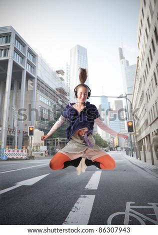 Young woman jumping while listening to music on a city street