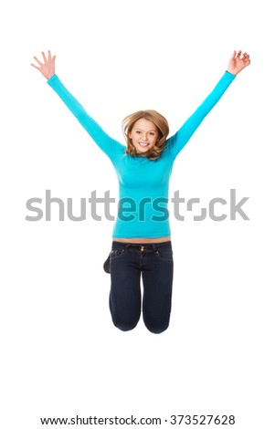 Young woman jumping with joy - stock photo