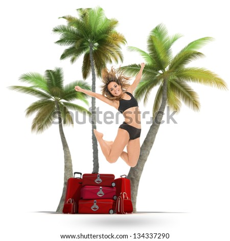 Young woman jumping with palm trees and a pile of luggage in the background - stock photo