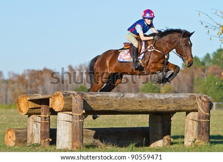 Young woman jumps a horse during practice on a cross country eventing course - stock photo