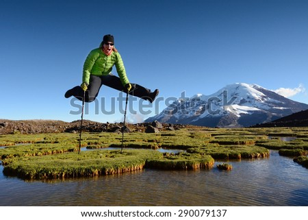Young woman jumps and enjoys beautiful view into high mountains, Chimborazo volcano, Ecuador, Andes, South America