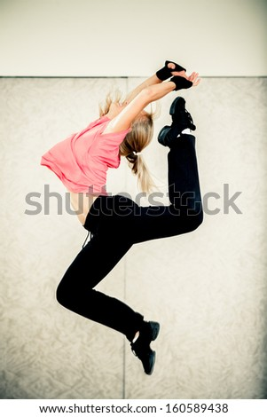 Young woman jumps while making aerobics exercises in a gym - stock photo