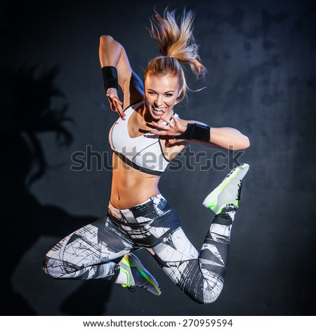 Young woman jumps while making aerobics exercises on gray background - stock photo