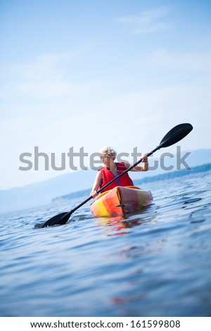 Young Woman Kayaking Alone on a Calm Sea and Wearing a Safety Vest - stock photo