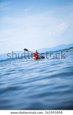 Young Woman Kayaking Alone on a Calm Sea and Wearing a Safety Vest