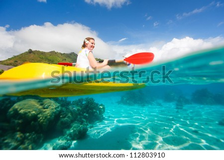 Young woman kayaking in a tropical lagoon - stock photo