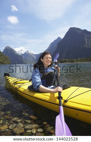 Young woman kayaking in lake with mountains in background - stock photo