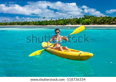 Young woman kayaking in the Ocean on Vacation on tropical Fiji island