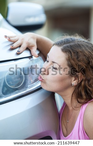 Young woman kissing her new car