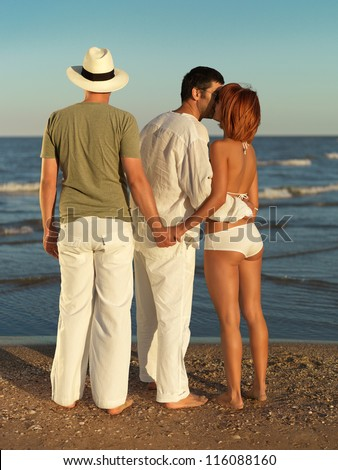 young woman kissing one man and holding hands with another, by the sea shore - stock photo