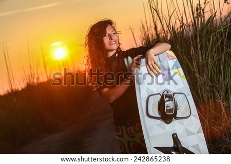 Young Woman Kitesurfer In Tall Grass Before Beach  - stock photo