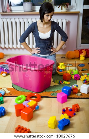 Young woman kneeling at container with toys and assembles strewn toys. She looks like thought about something. Front view.