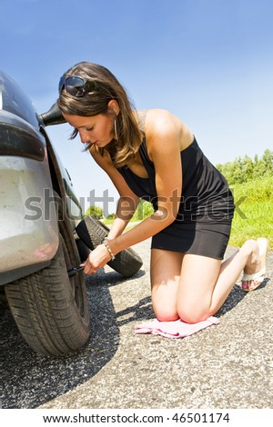 Young woman kneeling, changing the front tire of her car - stock photo