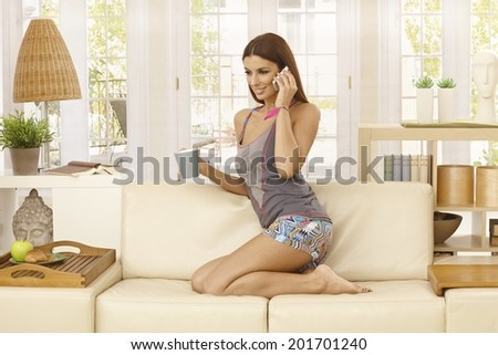 Young woman kneeling on sofa at home in living room, talking on mobilephone, drinking tea, smiling. - stock photo