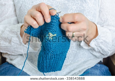 Young woman knitting woolen blue baby clothing - stock photo