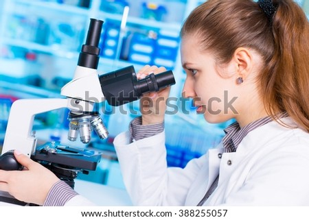 young woman. laboratory assistant watching biological experiment