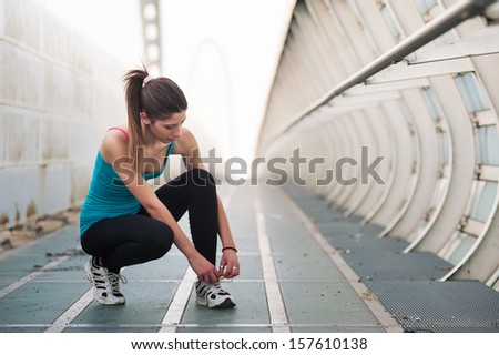 Young woman lacing her shoes outdoors on a modern bridge. Workout wellness concept. - stock photo