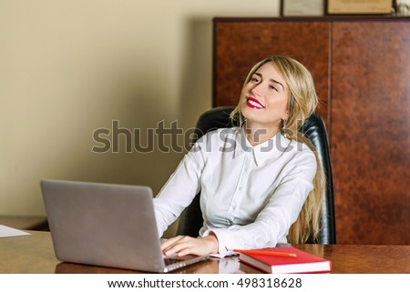 Young woman laughing and enjoying working at the office. Portrait of a businesswoman using laptop