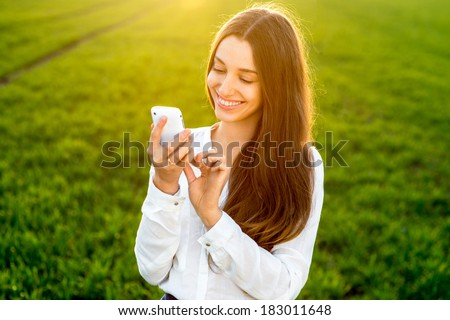 Young woman laughing and typing message in smart phone in the green field during spring or summer  - stock photo