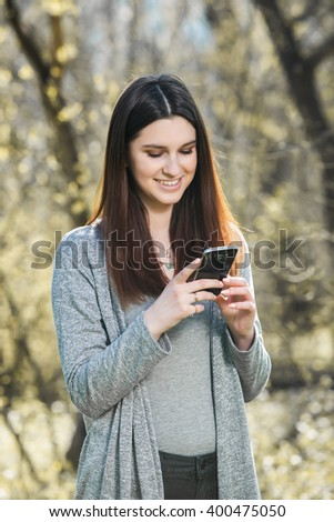 Young woman laughing and typing message in smart phone in the green field during spring or summer. Woman outdoors texting on her mobile phone. Girl with phone.