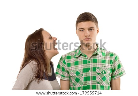 Young woman laughing at her own joke as he boyfriend stands looking unimpressed and unamused with a stony face, isolated on white - stock photo