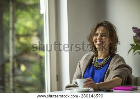 Young woman laughing while sitting near the window of his house. - stock photo