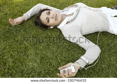 Young woman laying down on green grass, listening to music with headphones. - stock photo