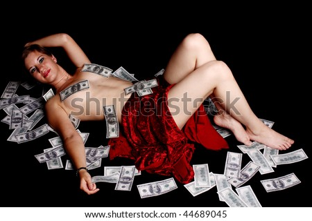 Young woman laying naked on a bed of cash.
