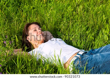 Young woman laying on a lawn or meadow in summer and is dreaming or sleeping - stock photo