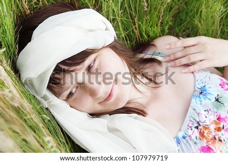 Young Woman Laying on Field Grass Portrait