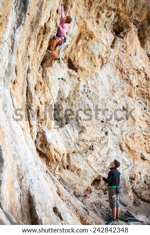 Young woman lead climbing on natural cliff, belayer watching her