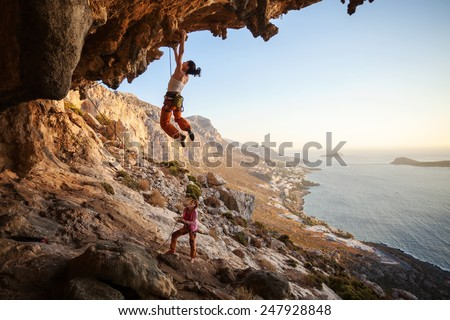 Young woman lead climbing on overhanging cliff, female partner belaying - stock photo