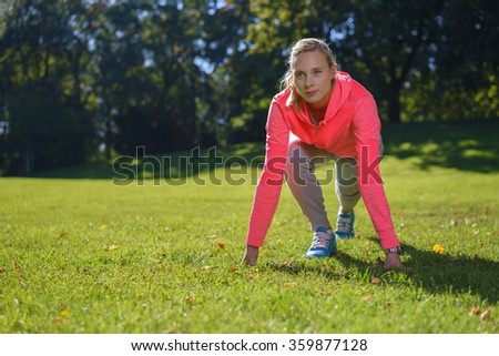 Young woman leading an active lifestyle exercising outdoors in a lush green park, low angle frontal view over grass with copy space - stock photo