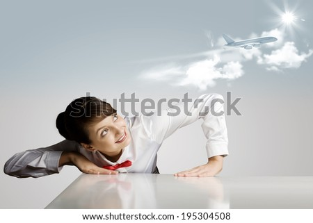 Young woman leaning above table and looking at airplane in sky - stock photo