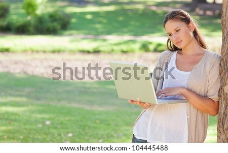 Young woman leaning against a tree while using a laptop