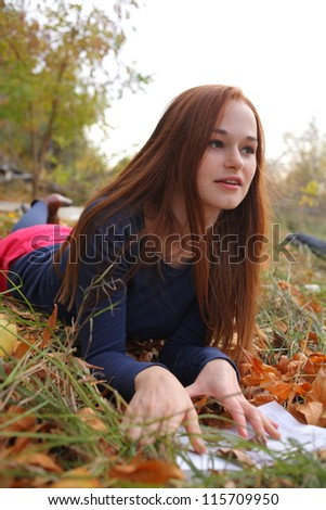 Young Woman  Leaning Book outdoors in autumn park