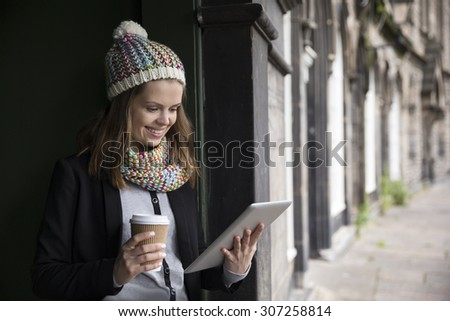 Young woman, leaning in a door way, using a tablet computer. Caucasian standing outdoors in the city. - stock photo