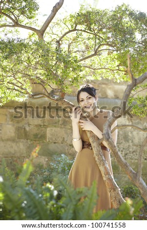 Young woman leaning on a tree in the park, smiling at camera. - stock photo