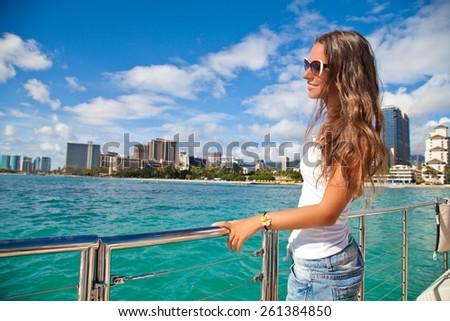 Young woman leaning on yacht railings, Oahu, Hawaii, USA. Girl on travel vacation holidays relaxing on Hawaiian resort. Summer cruise holidays - stock photo
