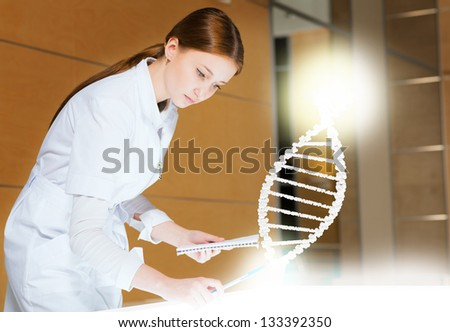 young woman leaning over a medical researcher illuminated table, the concept of modern technology in medicine - stock photo