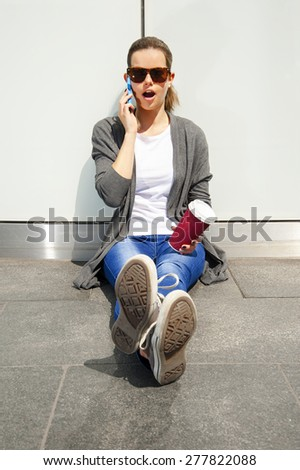 young woman leaning to wall in shock talking by phone in sunglasses - stock photo
