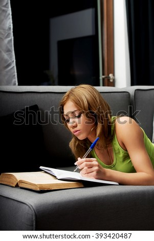 Young woman learning to exam on a sofa.