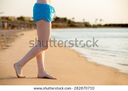 Young woman legs standing barefoot on the sunny sand beach at sea shore, relaxing in sunlight, copy space, close up - stock photo