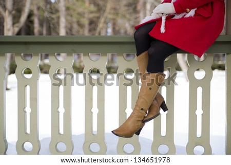 Young woman legs with boots at terrace boundary - stock photo