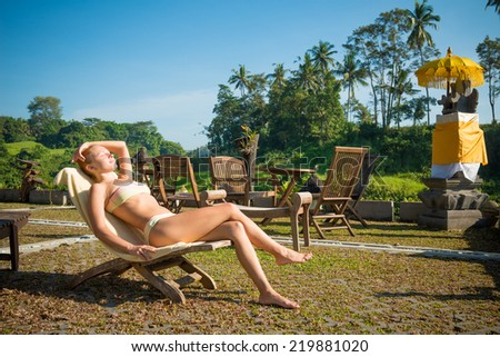 Young woman lie on sunbed and sunbathing at Indonesian resort - stock photo