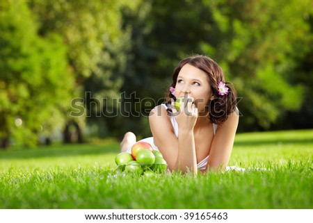 Young woman lies in a summer garden and eats an apple - stock photo