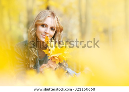 Young woman lies in maple leaves at autumn park - stock photo